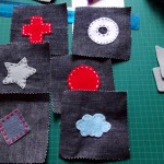 Use scrap wool and an upholstery needle to sew on the shapes.